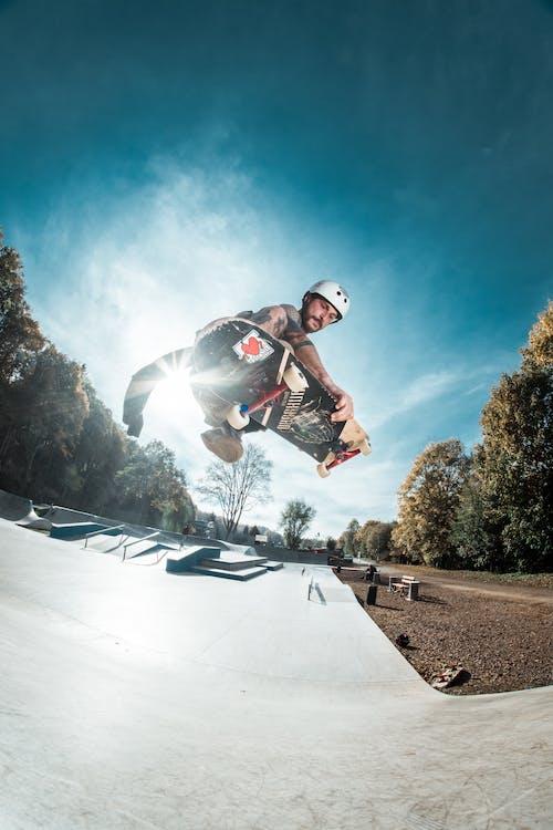 Man Skateboarding on Ramp Under Blue and White Sky