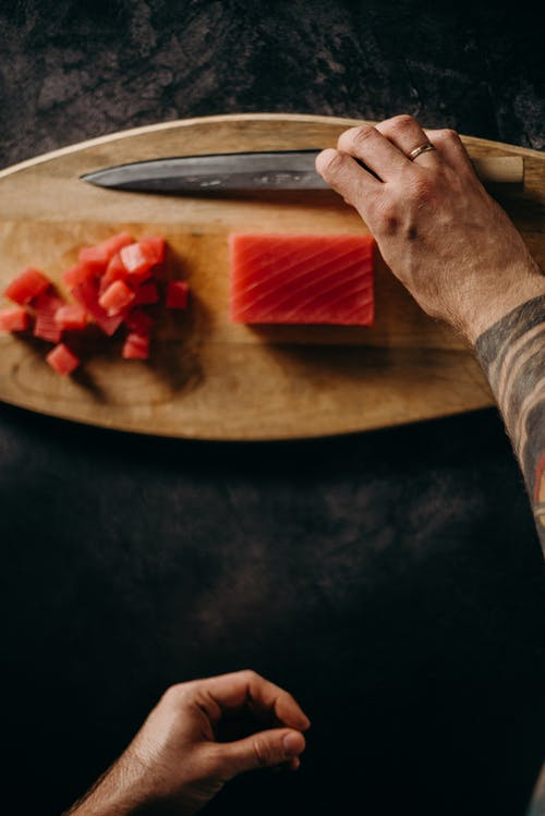Person Holding Knife Slicing Red Fruit