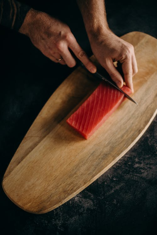 Person Slicing Fish Meat