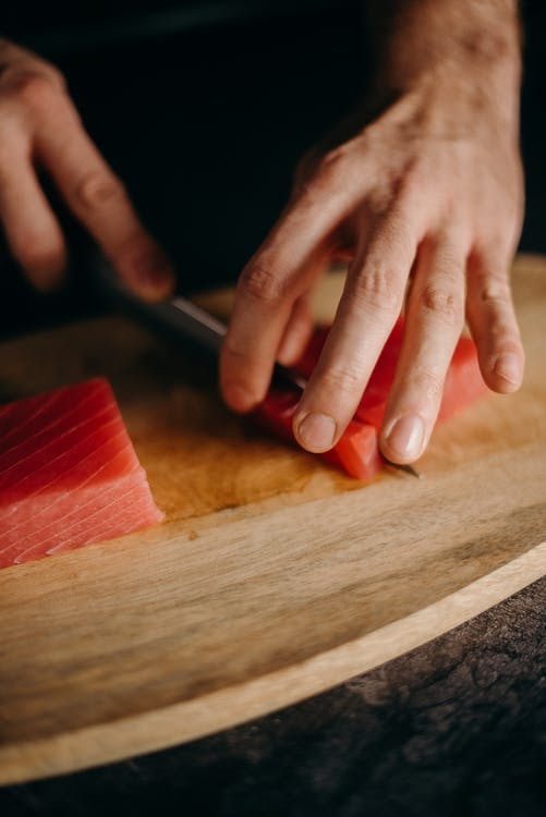 Person Holding Brown Wooden Chopping Board