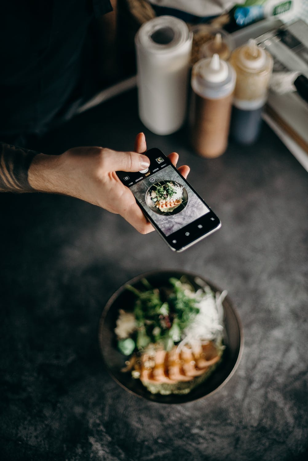 Pros and cons of instagram man taking photo of a bowl of food on mobile phone