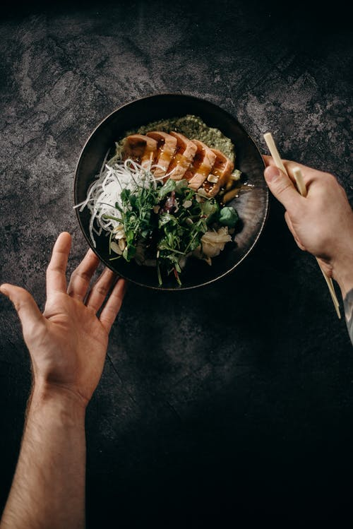Personne Tenant Un Bol En Céramique Noire Avec Salade De Légumes