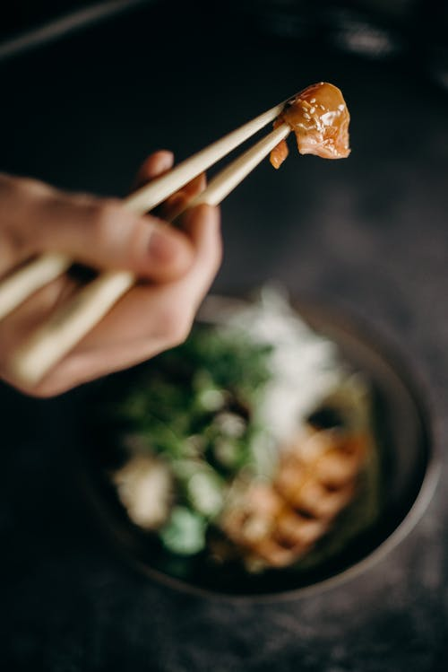 Person Holding Brown Wooden Chopsticks