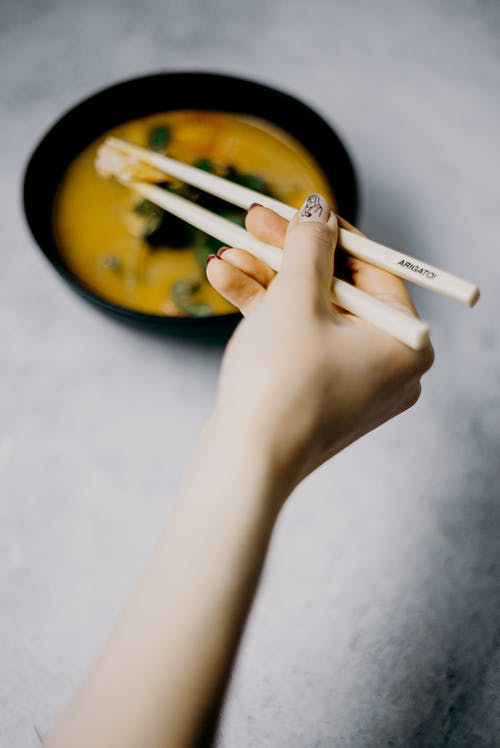 Photo Of Person Holding Chopsticks