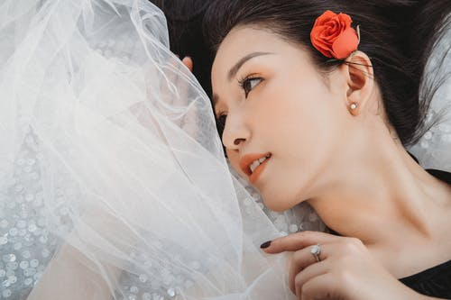 Ethnic woman lying on tulle fabric and looking away