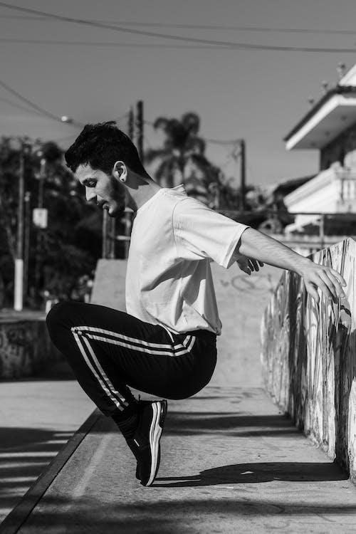 Man Tiptoeing While Sitting on Concrete
