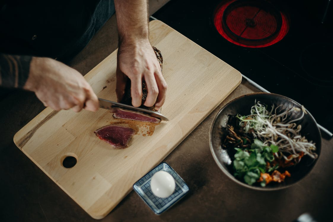Person Slicing Meat on Wooden Chopping Board