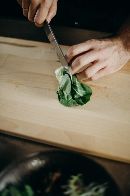 Person Slicing Green Leafy Vegetable