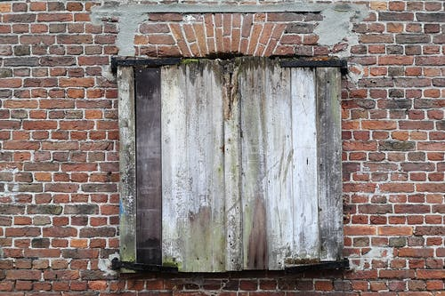 Free stock photo of brick wall, covered window, wood planks