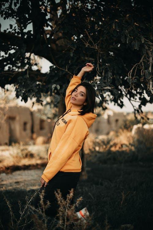 Mulher Com Capuz Amarelo Em Pé Ao Lado Da árvore