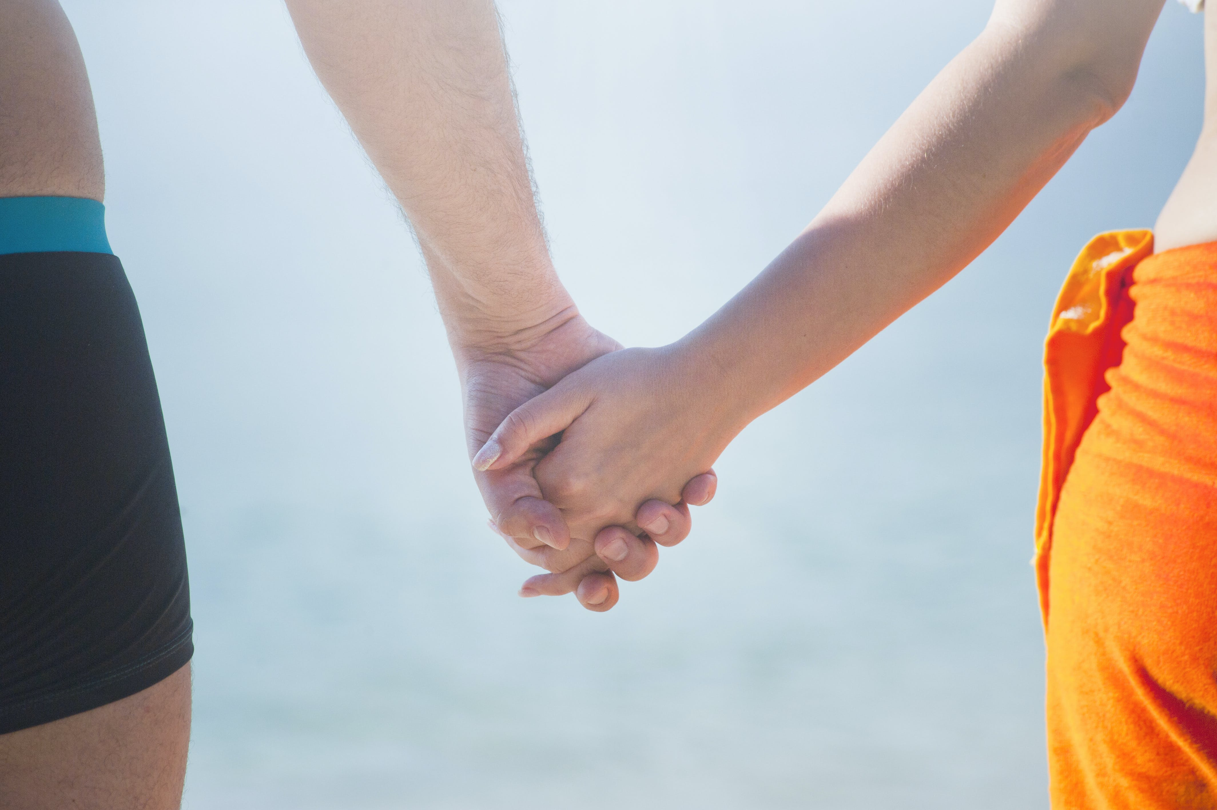 Midsection of Couple Holding Hands at Beach Against Sky