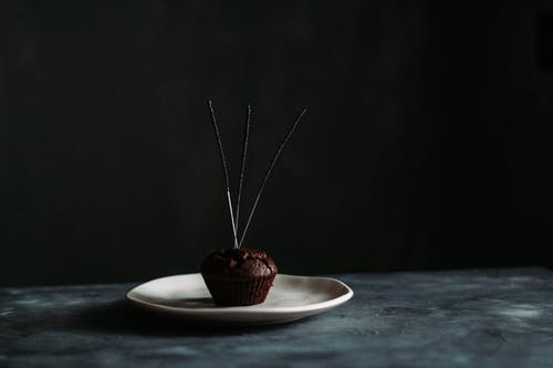 Chocolate muffin with firework sparklers on plate