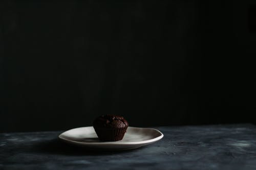 Chocolate muffin placed on ceramic plate on black background