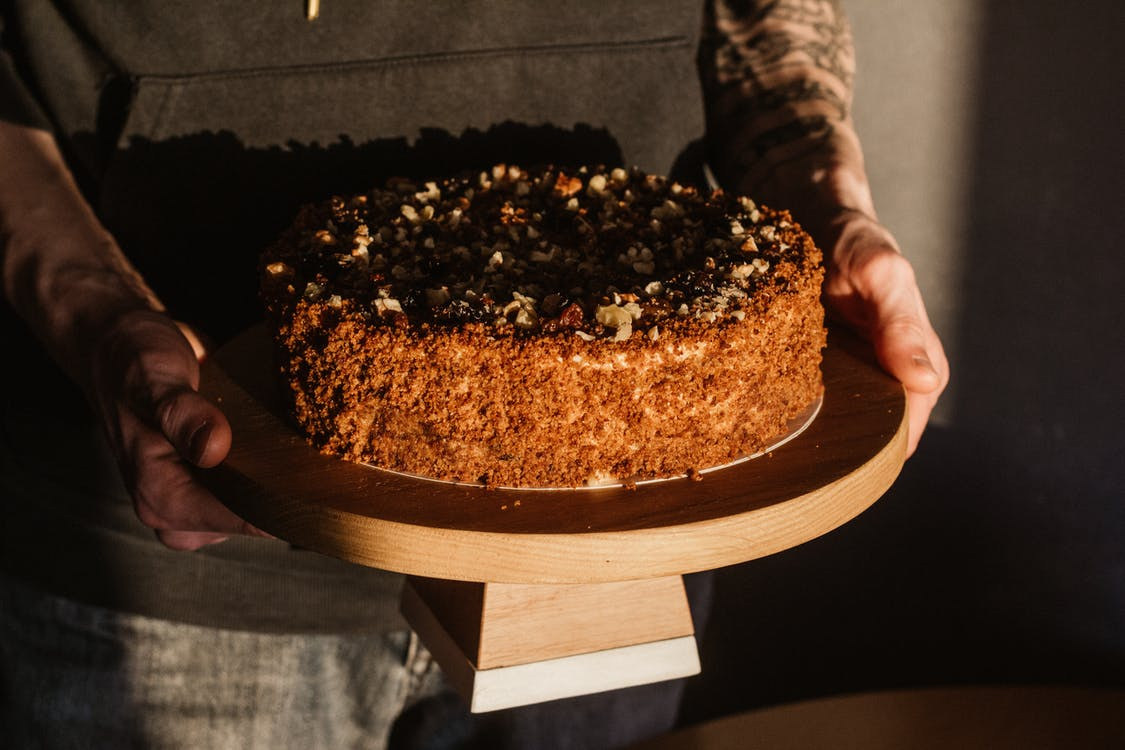Person Holding, A Delicious Looking Round Cake