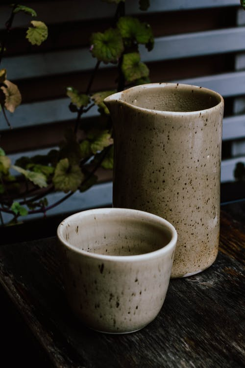 Modern jug and cup made of ceramic placed on wooden table