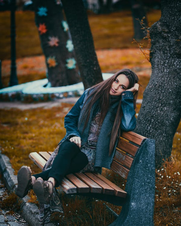 Woman Sitting on Bench Near Trees