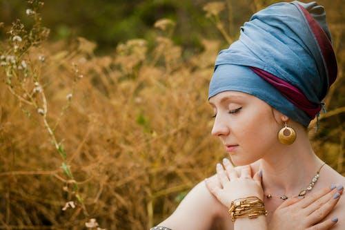 Wanita Mengenakan Sorban Biru Duduk Di Dekat Lapangan Coklat