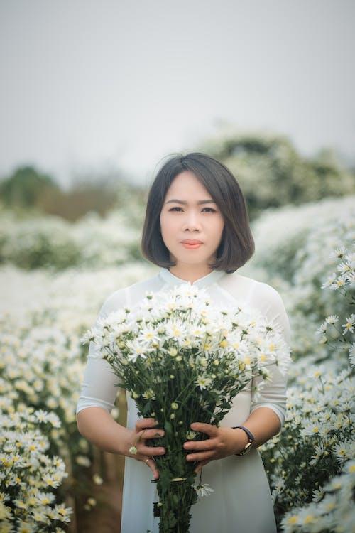 Woman Wearing White Dress Holding White Flowers