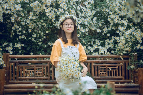 Girl Sits on Bench With Bouquet of Daisies