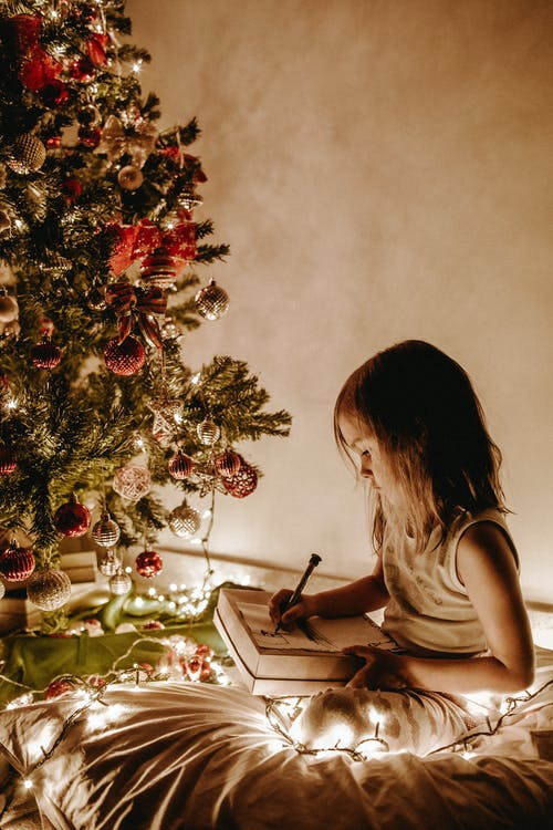 Photo of Girl Sitting Near Christmas Tree