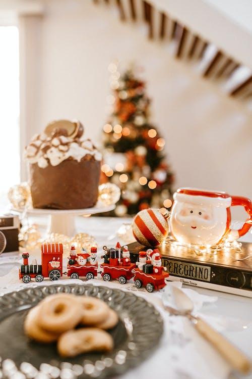 Fotografia Di Messa A Fuoco Selettiva Del Treno Di Natale E Della Tazza Di Babbo Natale Sul Tavolo