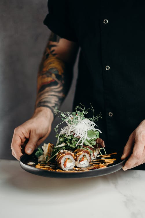 Person Holding A Plate Of Sushi Rolls