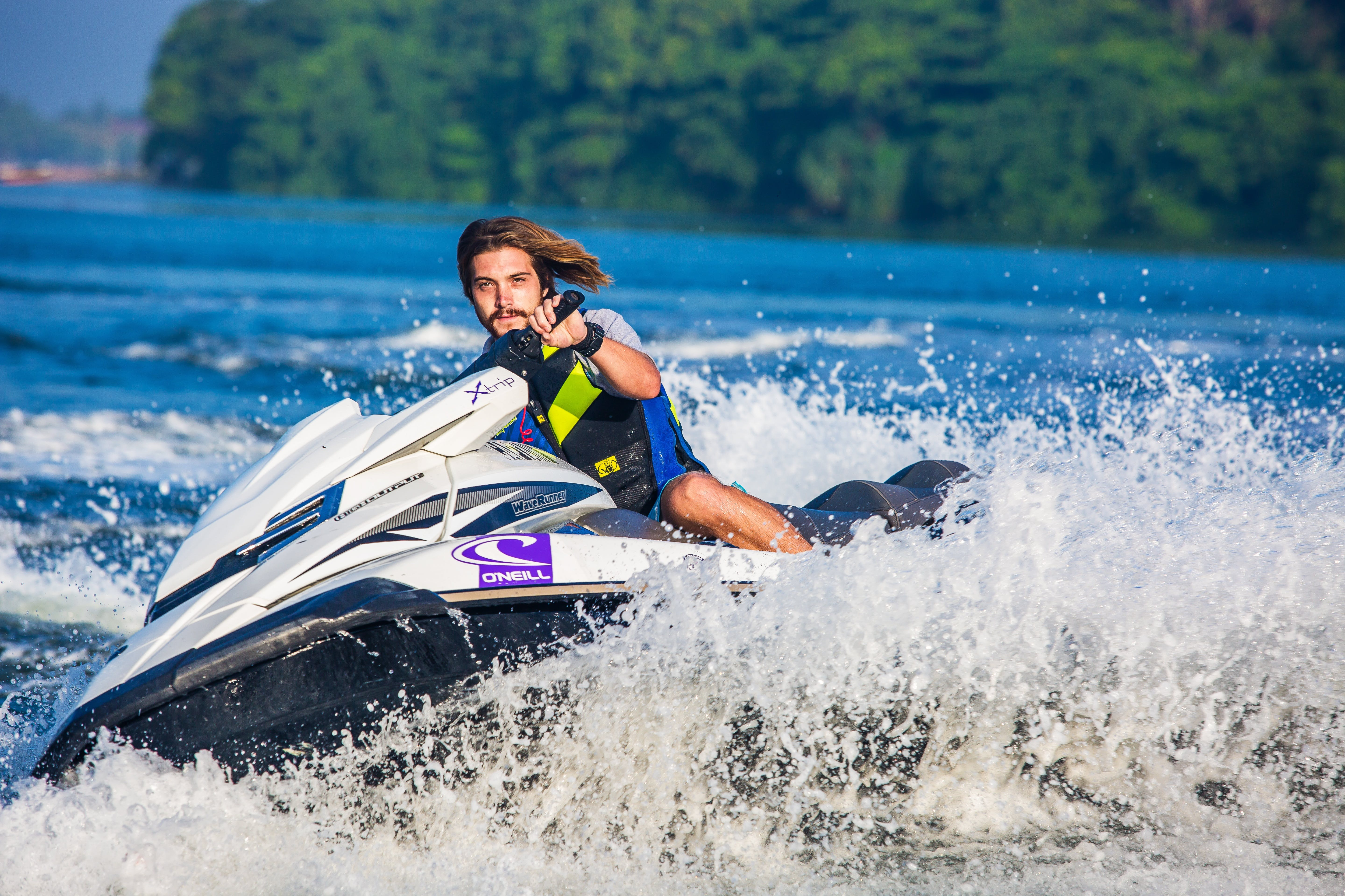 Man in Safety Vest Riding a Personal Watercraft during Daytime