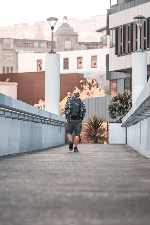 Person With Black Backpack Walking on Pathway