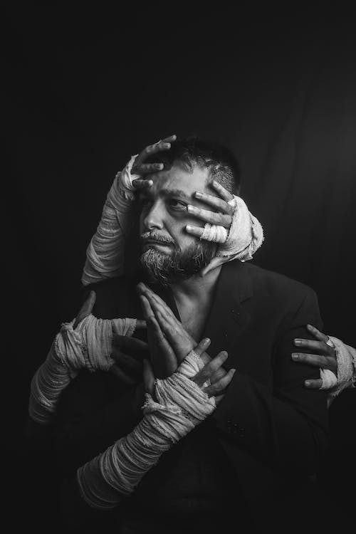 Monochrome Photo of Man With Hands All Over Him