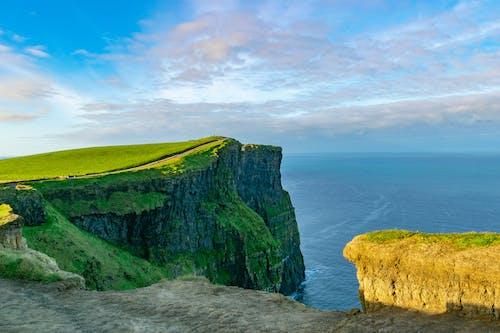 Kostenloses Stock Foto zu beeindruckende landschaft, blaue himmel, grasbewachsene klippe, hohe klippen