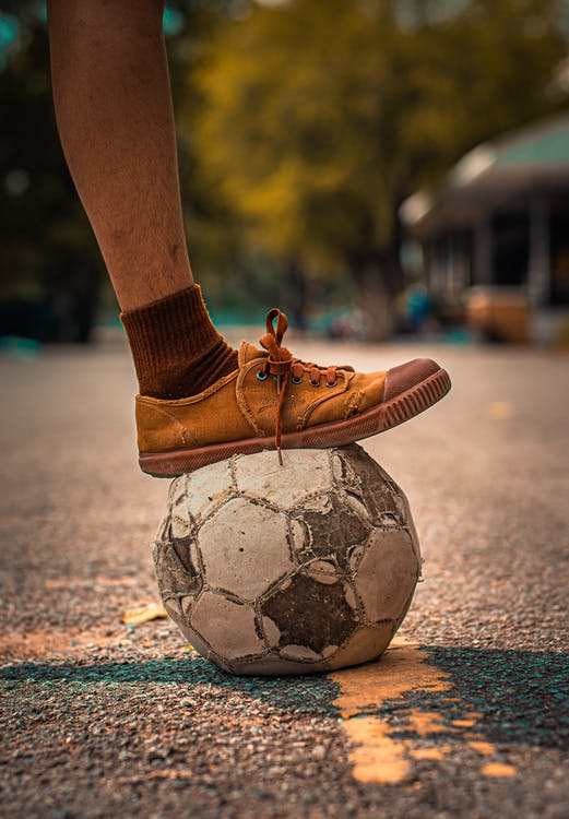 Person Stepping on a Soccer Ball
