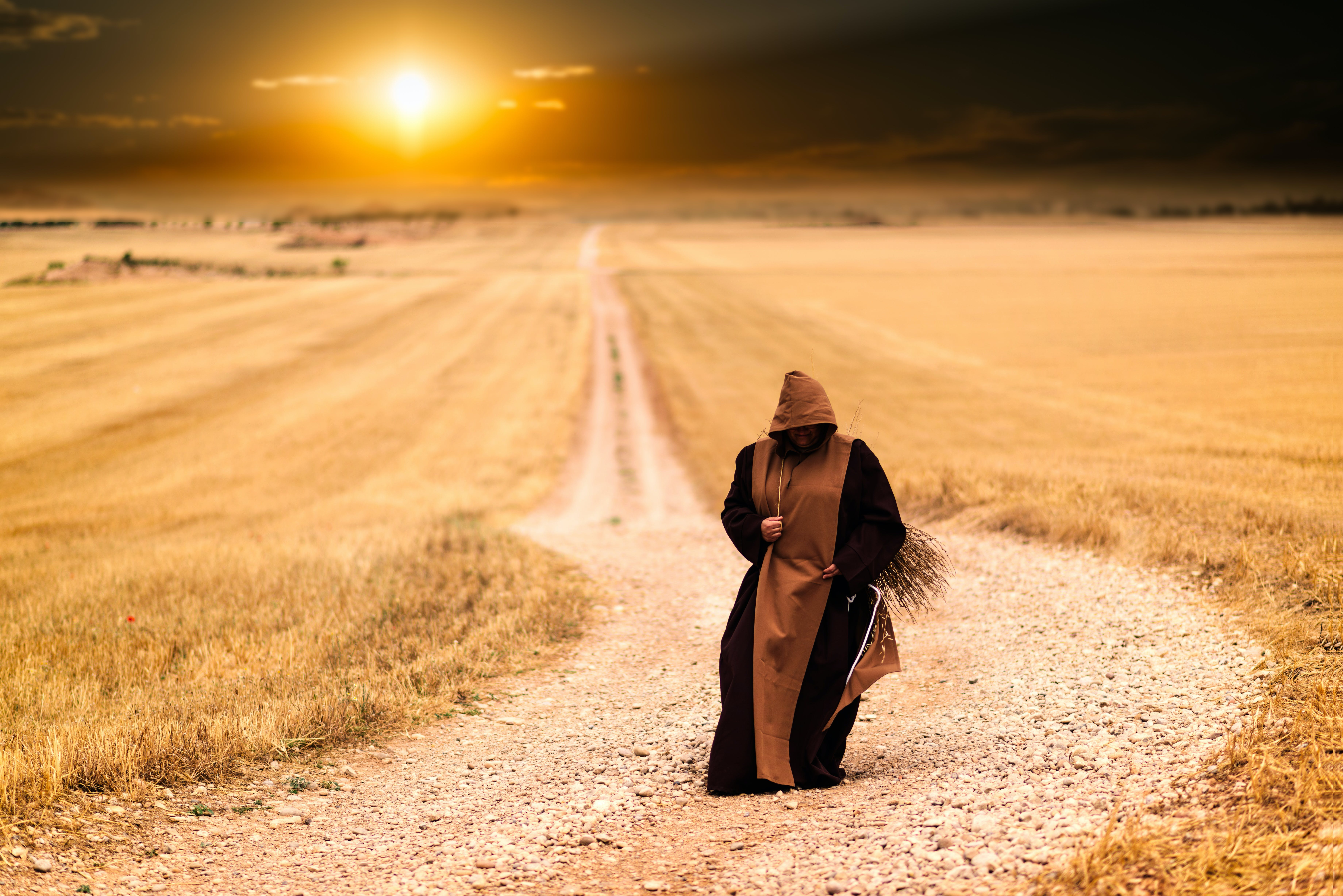Person in Brown and Black Robe in the Middle of the Road