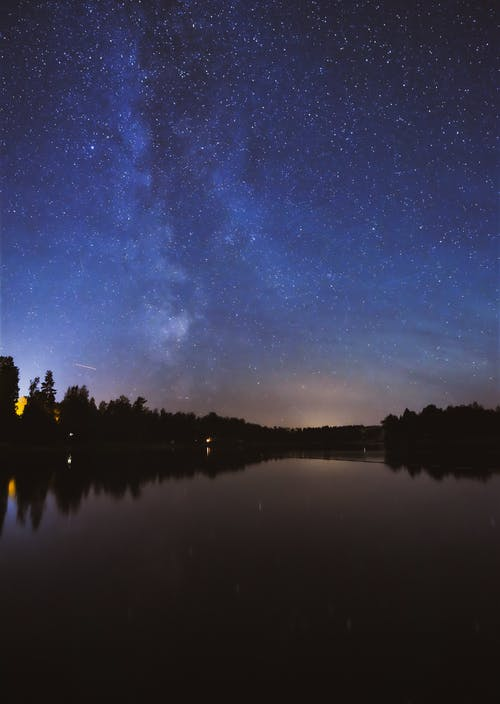 Landscape Photography of Tree's Reflection on Body of Water Under a Starry Night Sky