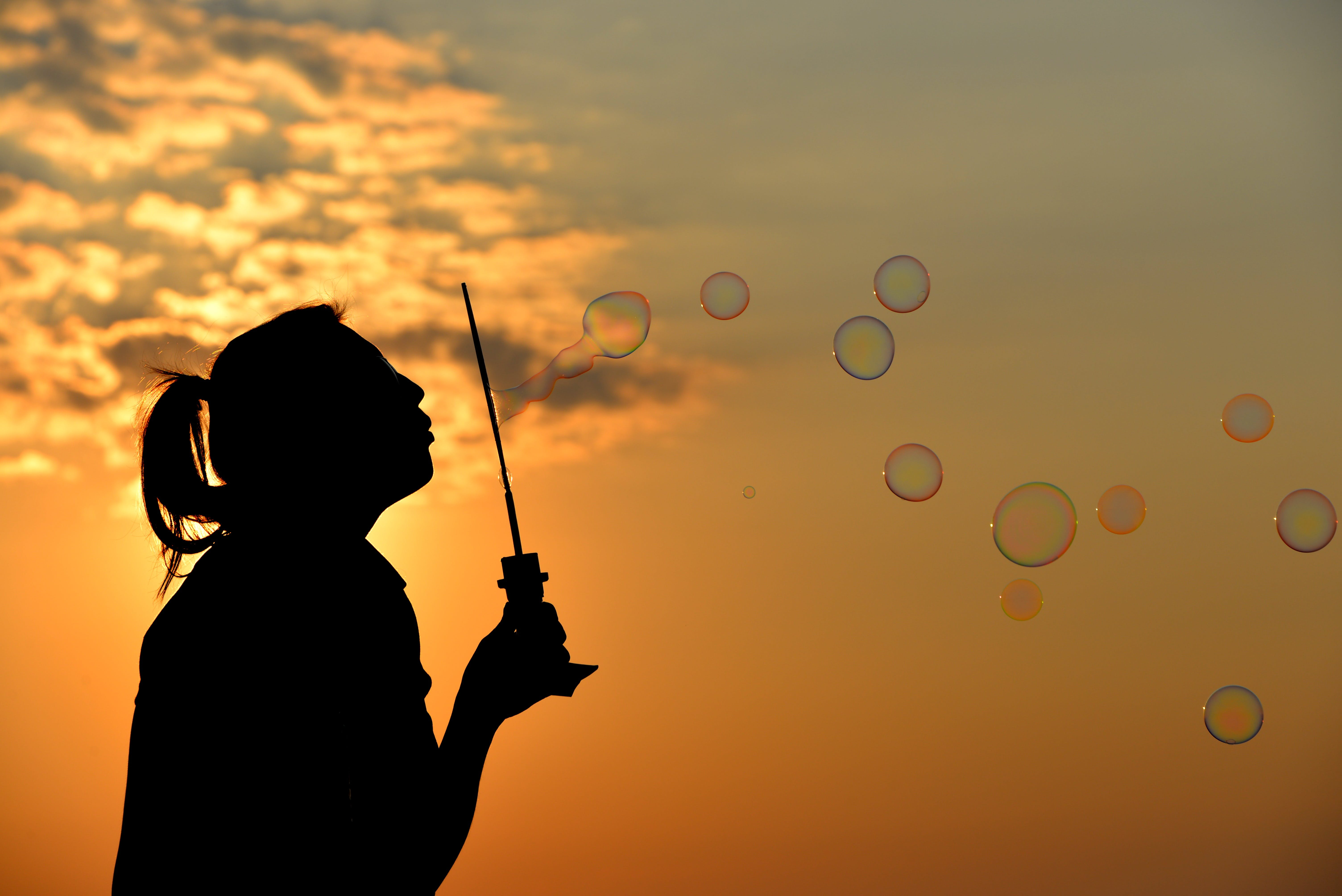 Silhouette Photo of Person Blowing Bubbles during Golden Hour