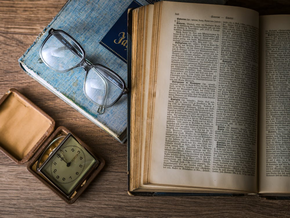 Opened Book Beside Sunglasses and Square Gray Clock Displaying 3:00 Time
