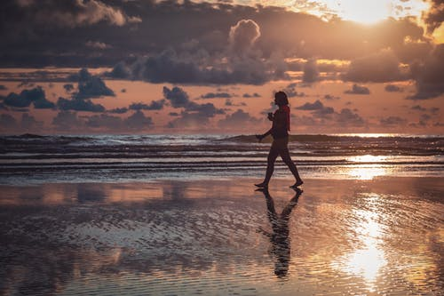 Silhouette of Walking Person on Seashore