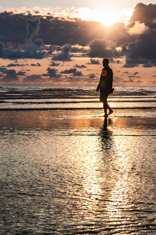 Man Walking on Seashore during Golden Hour