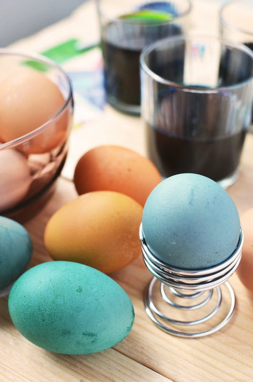 Brown and Blue Eggs Beside Drinking Glass