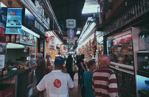 People Shopping At Stores In An Alley