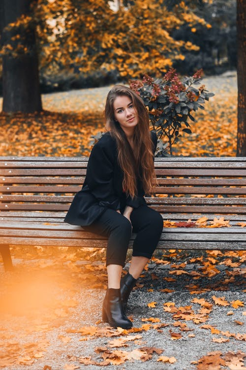 Woman Wearing Black Blazer Sitting on Wooden Bench