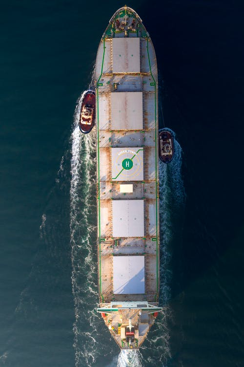 Aerial Photography of a Cargo Ship and Tag Boats