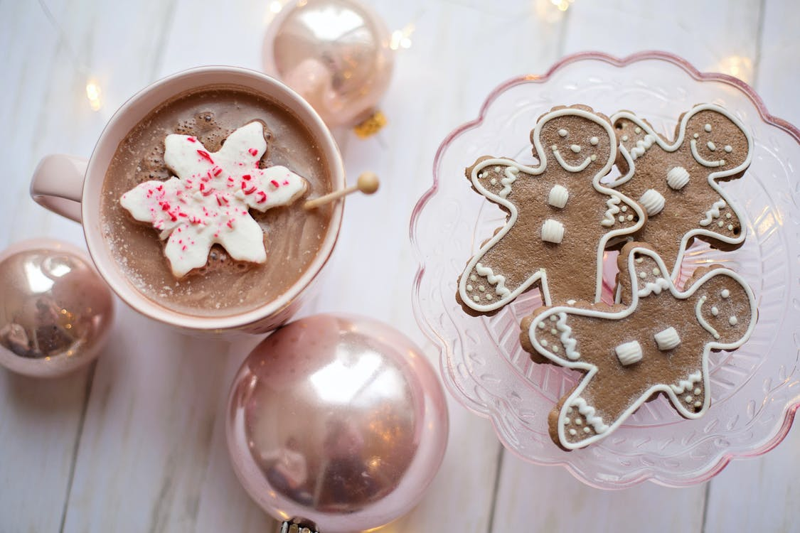 Top View Of Gingerbread on Glass Tray Beside A Cup of Drink And Christmas Balls