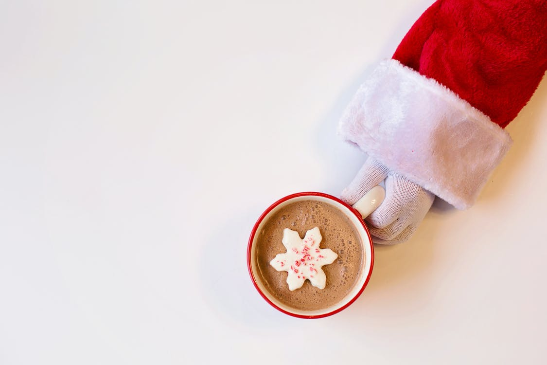 Mug of Chocolate Drink With Snowflake-Shaped Cookie On Top Held By A Person In Santa Suit