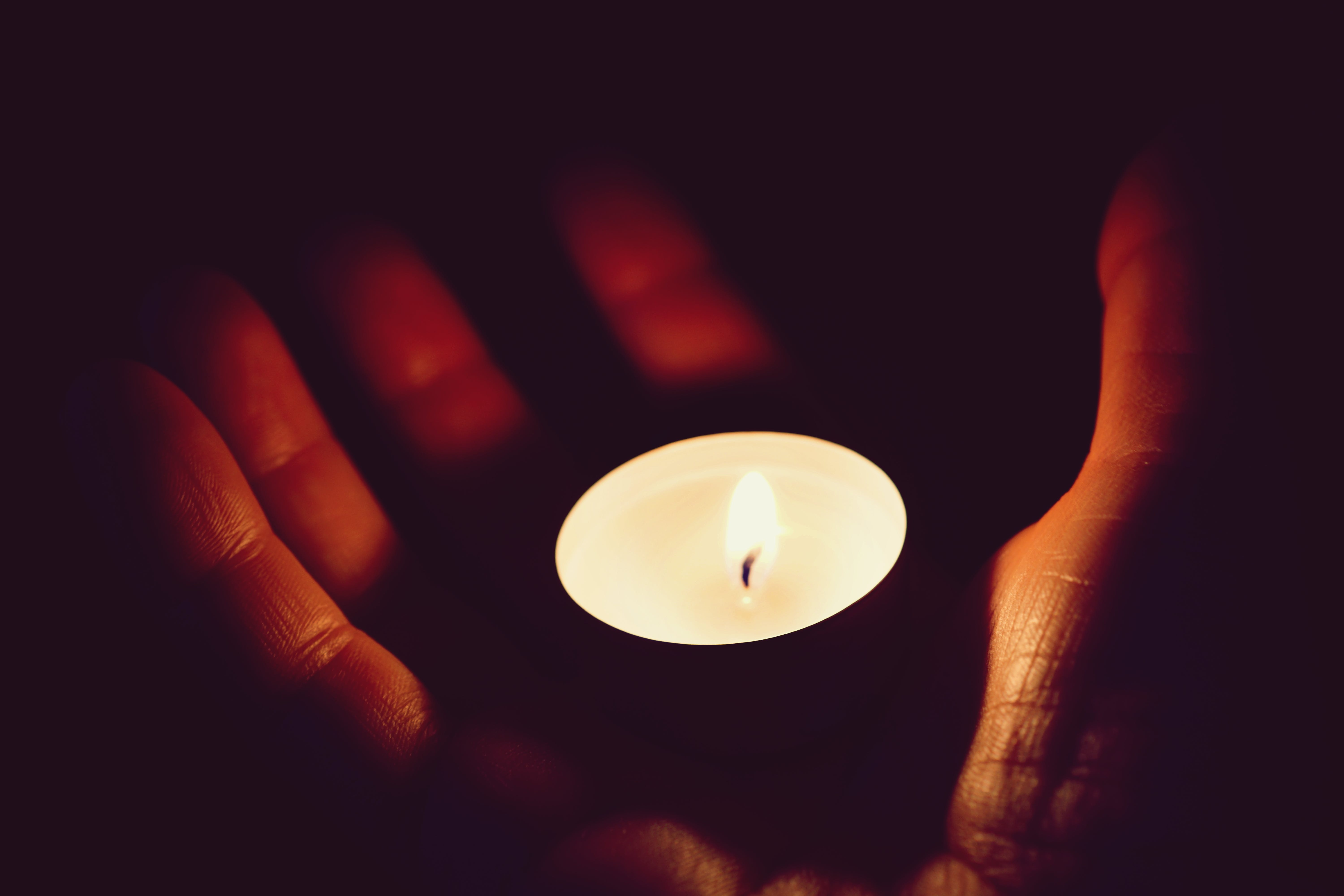 Lighted Tealight on Person Palm