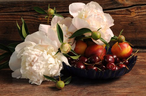 Witte Petaled Bloem Op Bruine Mand Naast Druiven