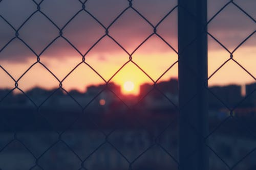 Close-Up Photo Of Chain Link Fence During Dawn