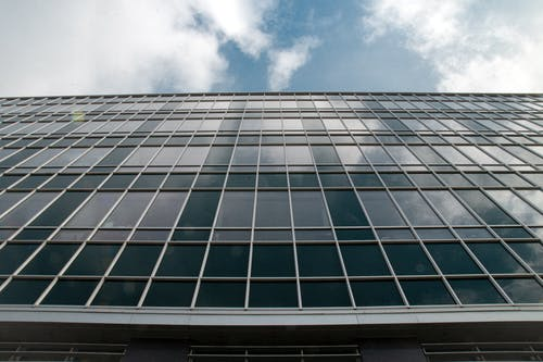 Low Angle Photography of Glass Building Under Blue Sky