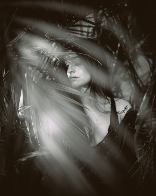 Greyscale Photography of Woman Behind Palm Leaves