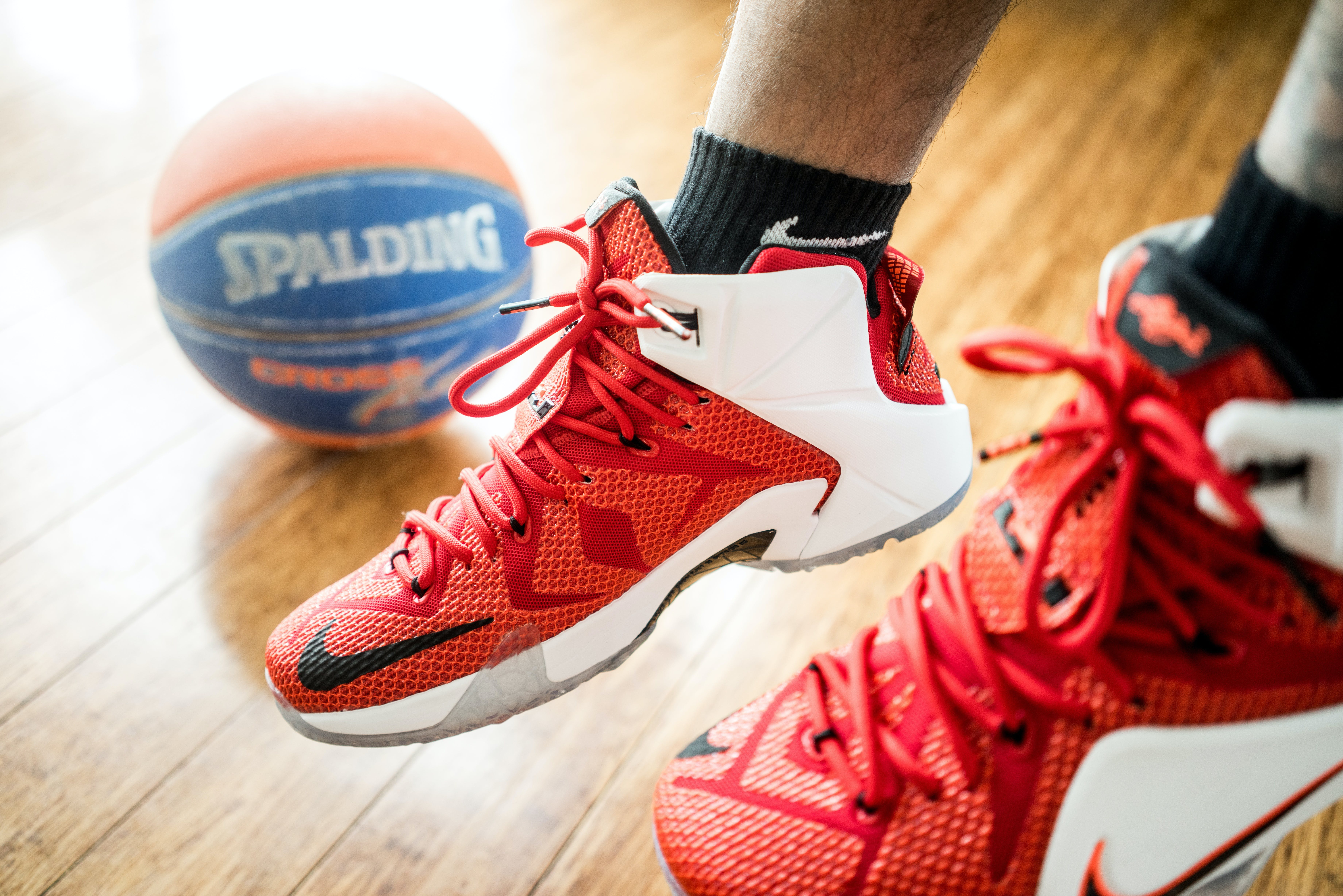 Person Wearing Pair of Red-and-white Nike Lebron 12 Shoes