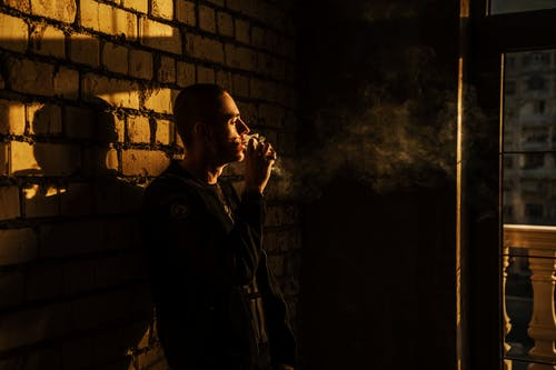Man Smoking and Leaning on Brick Wall